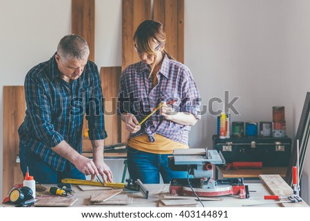 Young woman working at carpenter shop with here teacher. Small depth of field and selective focus. - stock photo