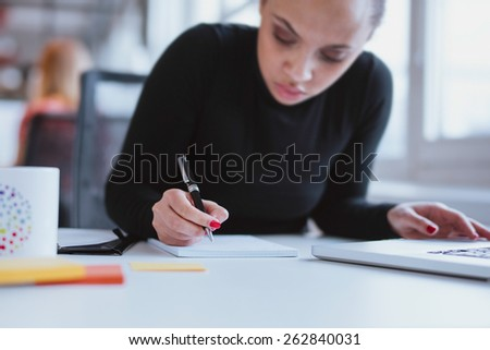 Young woman working at her desk taking notes. Focus on hand writing on a notepad. - stock photo