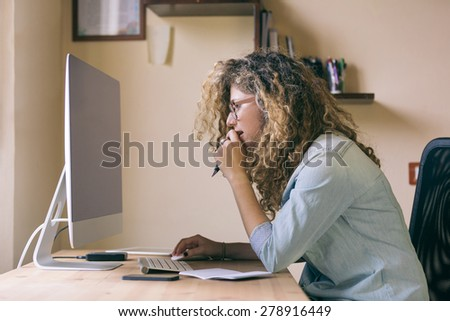Young woman working at home or in a small office, vintage hipster clothing, curly hair. On the wooden desk there are a computer, a digital tablet, a smart phone and a notepad. - stock photo