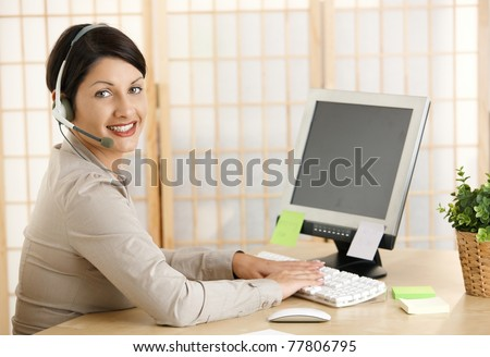 Young woman working at home, talking on headset, using computer. Copyspace on blank screen.? - stock photo