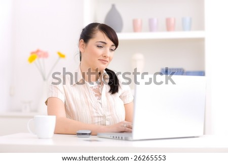 Young woman working at home using a laptop computer. - stock photo