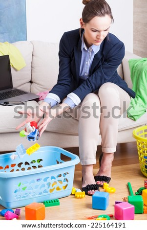 Young woman working from home and cleaning up toys - stock photo