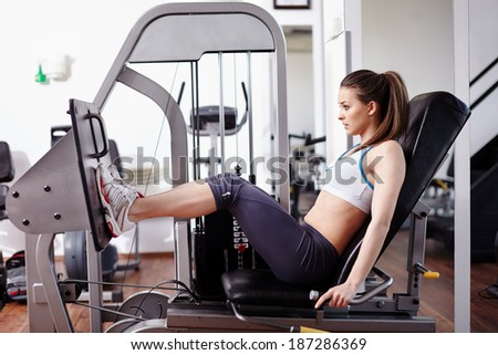 Young woman working her quads at machine press in the gym - stock photo