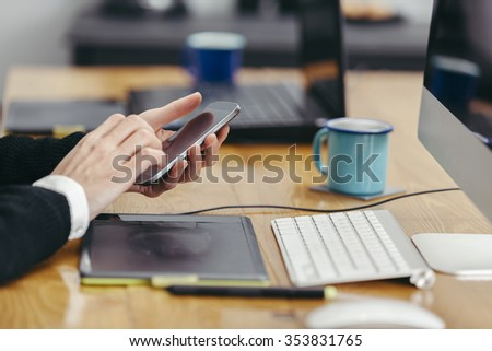 young woman working in a homely office and using her smartphone - stock photo