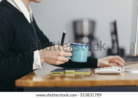 young woman working in a homely office with her coffee and stuff - stock photo