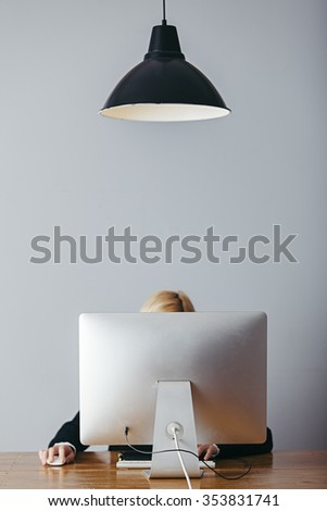 young woman working in an office  with a lamp and a computer on wooden desk - stock photo