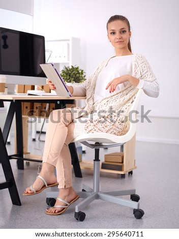 Young woman working in office, sitting at desk