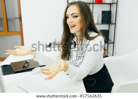Young woman working in office, sitting at desk, using computer with asking gesture - stock photo