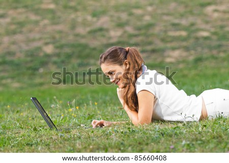 Young woman working in the park on laptop