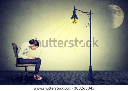 Young woman working long hours using laptop