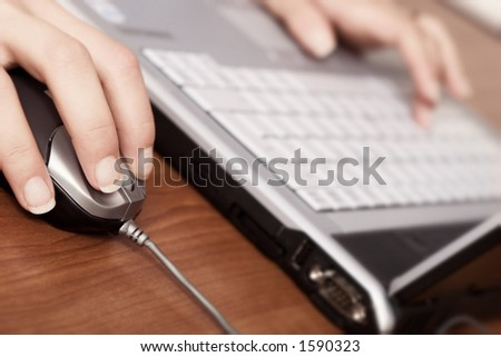 Young woman working on a laptop, close-up on the hand and mouse - stock photo