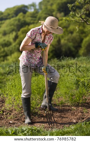 Young woman working on garden outdoor - stock photo