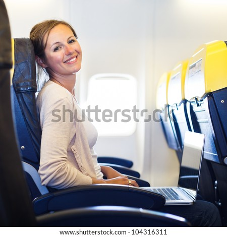 Young woman working on her laptop computer on board of an airplane during the flight - stock photo