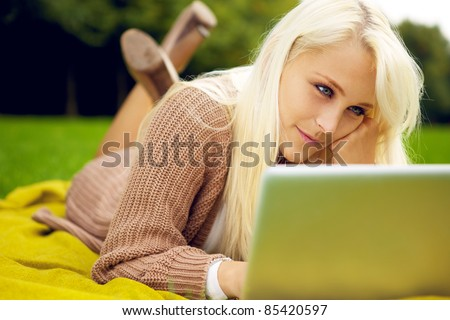 Young woman working on her notebook in park - stock photo