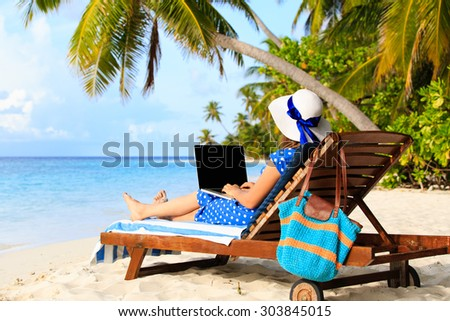 young woman working on laptop at tropical vacation - stock photo