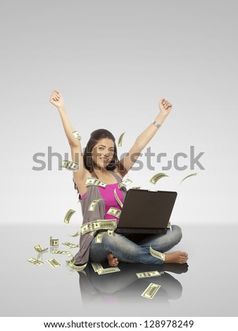 young woman working on laptop from which dollar note is coming out - stock photo