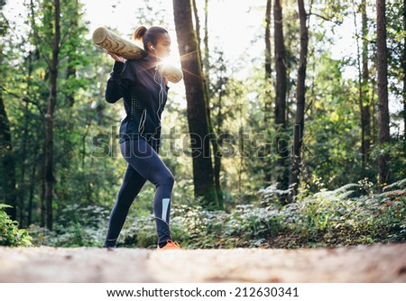 Young woman working out in forrest lifting weights - stock photo