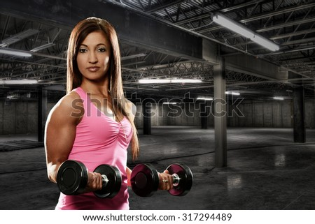 Young Woman working out  inside a dark building - stock photo