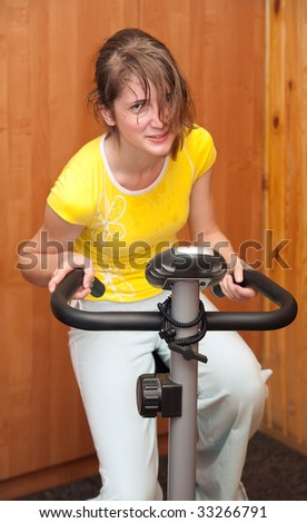 Young woman working out on exercise bike at the gym. - stock photo