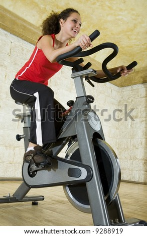 Young woman working out on exercise bike at the gym. Low angle view. - stock photo
