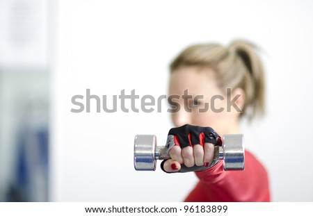 Young woman working out with dumbbell in her hand. Focus is on dumbbell and her face is blurred. Copy space is to the left. - stock photo