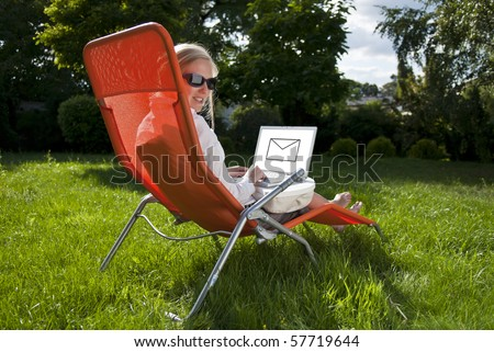 young woman working outside on computer, in the garden - stock photo