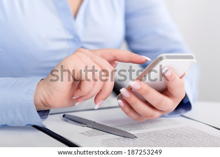Young woman working with a mobile phone above the contract and pen