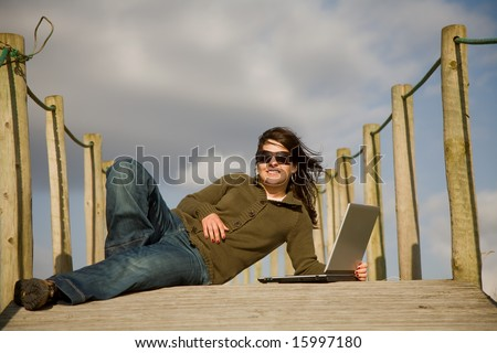 young woman working with computer at the beach