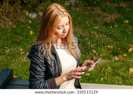 Young woman working with digital  tablet in internet, internet concept, copy space. Campus park.  - stock photo