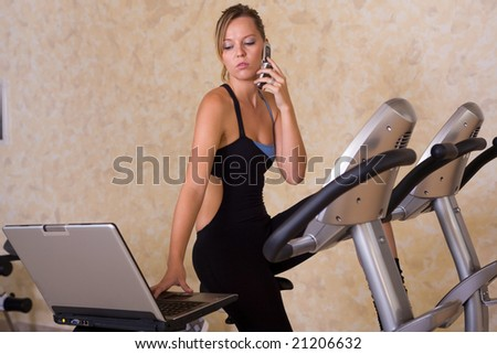 young woman working with laptop and phone while exercising - stock photo