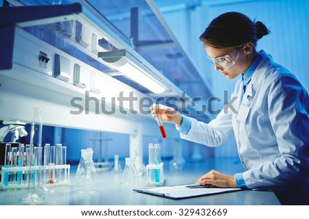 Young woman working with liquids in glassware - stock photo