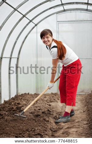 young woman working with rake in hothouse
