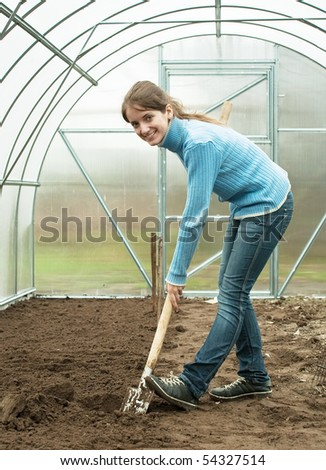 young woman working with shovel in hothouse - stock photo