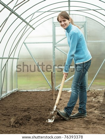 young woman working with shovel in hothouse