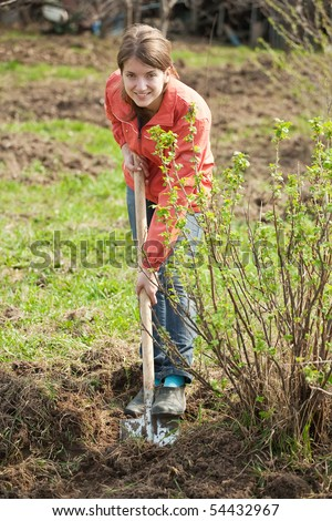 young woman working with shovel in orchard