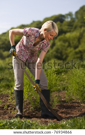 Young woman working with shovel on the garden outdoor - stock photo