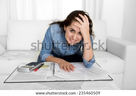 young woman worried at home in stress at living room accounting debt bills expenses with calculator feeling desperate on payments in bad financial situation concept