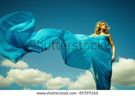 Young woman wrapped in a long piece of light fabric fluttering in the wind - stock photo