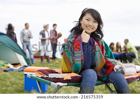 Young woman wrapped in blanket attending outdoor festival - stock photo