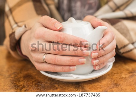 Young woman wrapped in plaid warming hands with a tea pot in a street cafe on a cold day