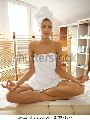 Young woman wrapped in towel doing yoga, eyes closed - stock photo