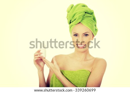 Young woman wrapped in towel holding deodorant. - stock photo