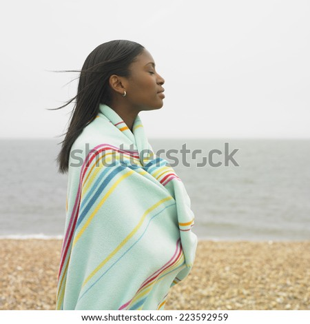 Young woman wrapped in towel standing on beach - stock photo