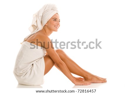 Young woman wrapped towels sitting isolated on white background