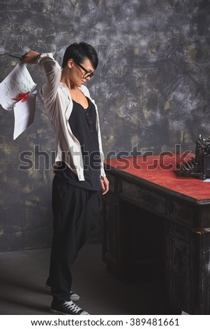 Young woman writer in hard creative process, looking for new ideas, throwing papers, documents in art space with wooden table, grey background - stock photo