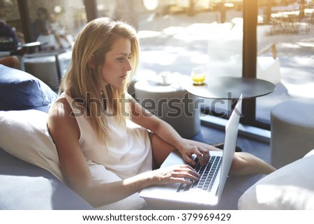 Young woman writer keyboarding text for a new book via laptop computer while sitting in co-working cafe,pretty female student searching information on net-book during lunch break in modern coffee shop - stock photo