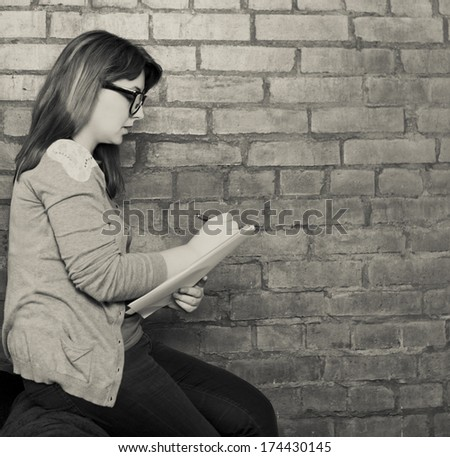 Young woman writer working in the loft. Black and white - stock photo