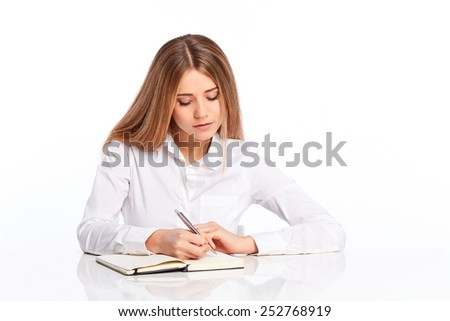 Young woman writes in a diary on a white background - stock photo