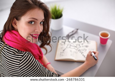 Young woman writes to diary on a white table - stock photo