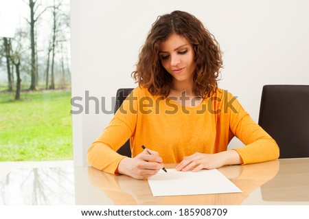 Young woman writing a letter with a nature in the background - stock photo